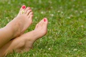 Woman's bare feet in grass with daisies between toes